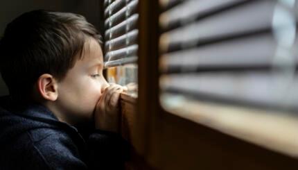 Small sad boy looking through the window during Coronavirus isolation.